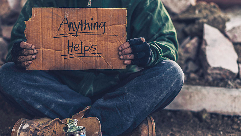"Mann am Betteln mit Schild ""Anything helps"""