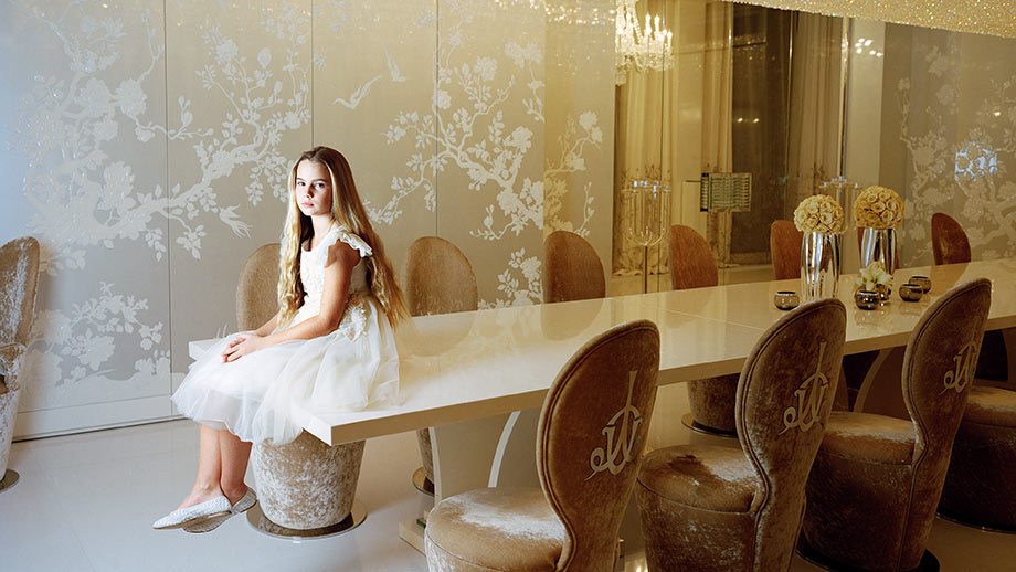 Young girl sitting on a dining table in a luxurious room.